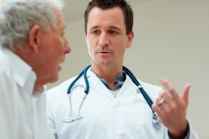 Handsome young doctor speaking to a senior man , explaining the diagnosis